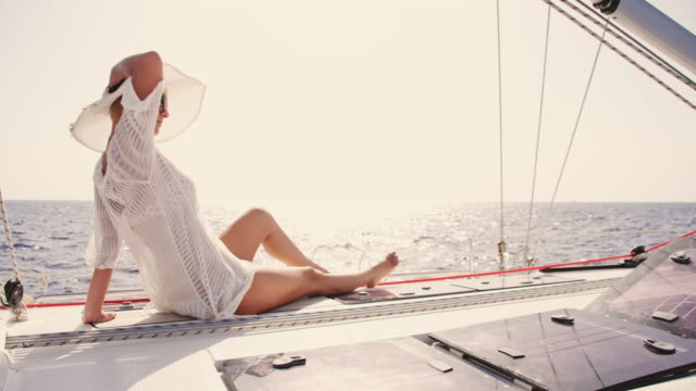 slo mo trendy woman enjoying the wind on a sailboat - sunbathing stock videos and b-roll footage