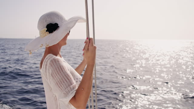 slo mo trendy woman enjoying the wind on a sailboat - sun hat stock videos & royalty-free footage