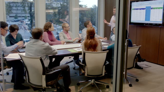 Trendy young businessman leads meeting in corporate boardroom, encourages round of applause (dolly shot)