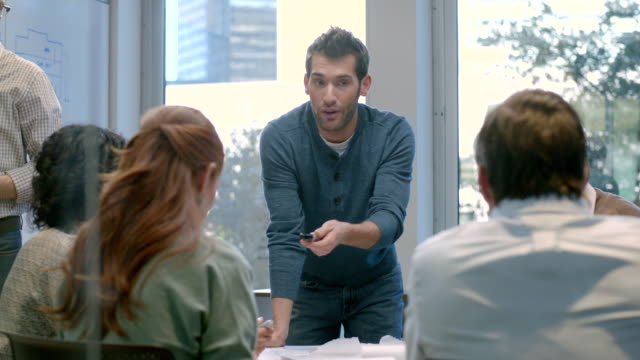 vídeos de stock e filmes b-roll de trendy young businessman leads meeting in office conference-room (dolly shot) - ideas
