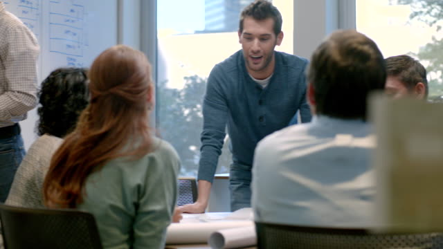 Trendy young businessman leads meeting in office conference-room, general agreement (dolly shot)
