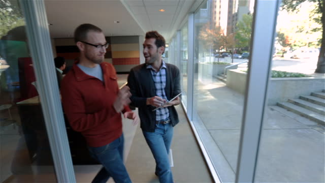 vídeos de stock, filmes e b-roll de trendy young businessman shares funny video on tablet with colleague as they walk up office hallway (tracking shot) - plano geral ponto de vista
