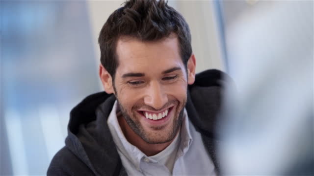 Trendy young businessman smiles as co-workers throw out ideas and write on white-board table