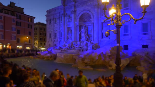 Trevi Fountain at night. Trevi Fountain in Rome is one of Italy's most famous landmarks and often surrounded by tourists (people blurred for commercial use)