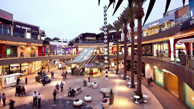 ws t/l tri level open courtyard of santa monica place luxury shopping mall at dusk with escalators connecting three floors of shops and restaurants / santa monica, california, usa   - santa monica bildbanksvideor och videomaterial från bakom kulisserna
