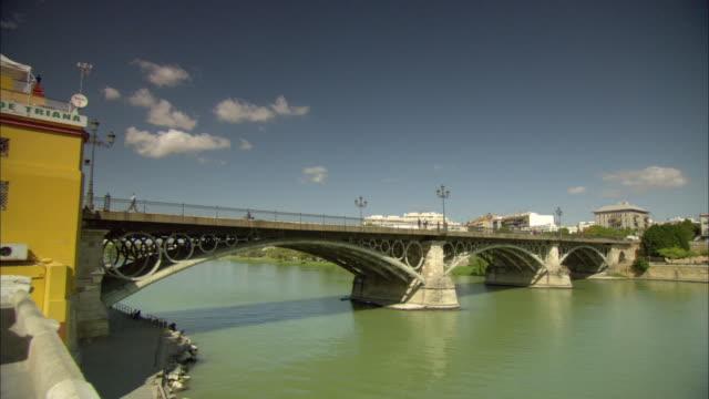 vídeos de stock e filmes b-roll de ws triana bridge crossing river guadalquivir / andalusia, spain - ponte