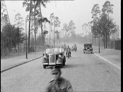 vidéos et rushes de triangular flag with nazi sign ii m29 members of the nskk unit in uniform pass by the camera in cars and on motorcycles - nazisme