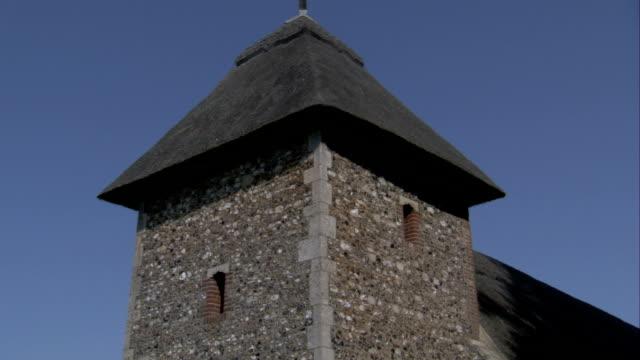 vídeos de stock e filmes b-roll de a triangular roof tops st mary's church in thornham parva, suffolk. available in hd. - telhado de palha