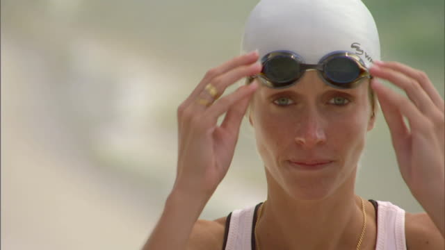 cu triathlete swimmer wearing swim cap and adjusting her swimming goggles / langebaan, south africa - triathlete stock videos and b-roll footage