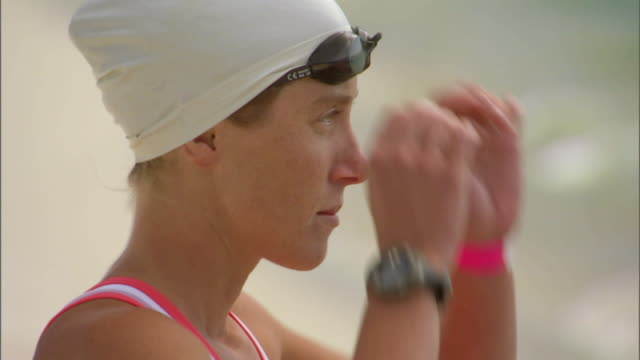 cu triathlete swimmer wearing swim cap and adjusting her swimming goggles / langebaan, south africa - swimming cap stock videos and b-roll footage