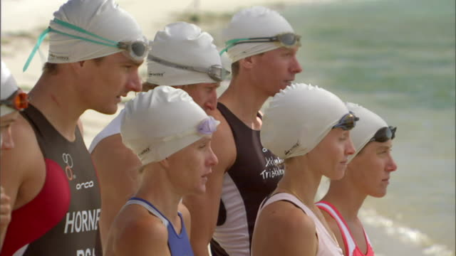 cu triathlete swimmers wearing swim caps and adjusting their swimming goggles before running into water / langebaan, south africa - swimming cap stock videos and b-roll footage