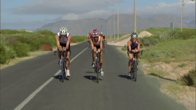 TS WS Triathletes cycling on remote road during race / Strandfontein, Western Cape Province, South Africa