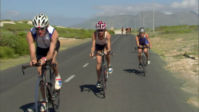 TS WS PAN Triathletes cycling on remote road during race, then one woman pulls ahead / Strandfontein, Western Cape Province, South Africa
