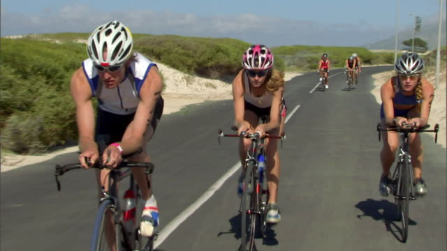 TS WS Triathletes cycling on remote winding road during race / Strandfontein, Western Cape Province, South Africa