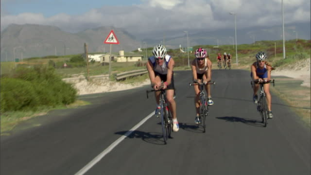 TS WS Triathletes cycling on winding road during race / Strandfontein, Western Cape Province, South Africa