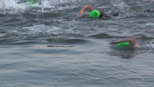 stockvideo's en b-roll-footage met triathletes in the nyc triathlon swim in hudson river cycle on west side drive and run in central park calm water to pack of swimmers - salmini