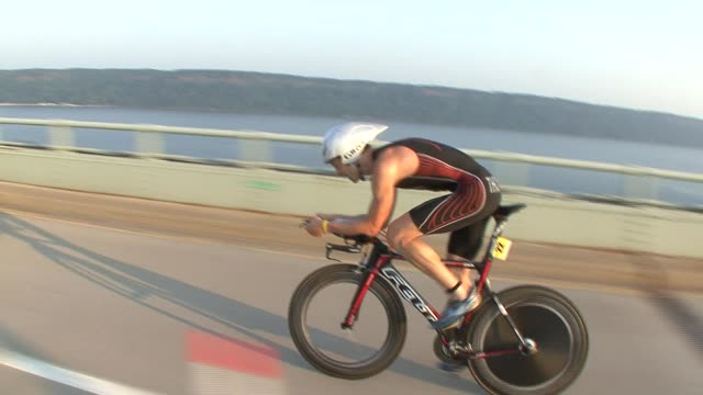 stockvideo's en b-roll-footage met triathletes in the nyc triathlon, swim in hudson river, cycle on west side drive and run in central park. cyclist on west side drive on henry hudson... - salmini