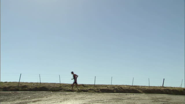 WS Triathletes running on remote road during race / Cape Town, South Africa
