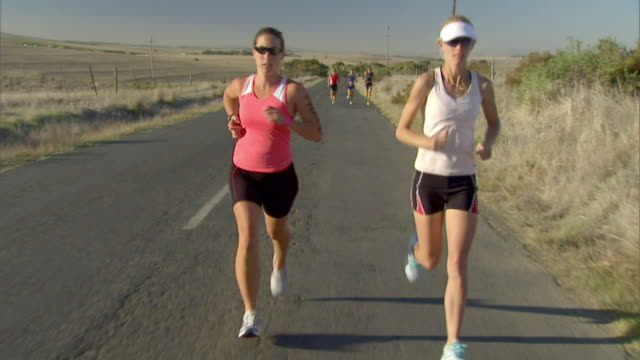 ts ws triathletes running on remote road during race / cape town, south africa - sunglasses点の映像素材/bロール