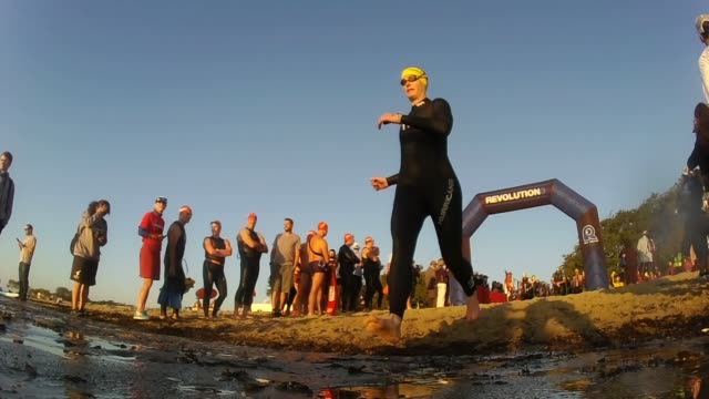 triathletes start on beach and head to water - salmini stock videos and b-roll footage