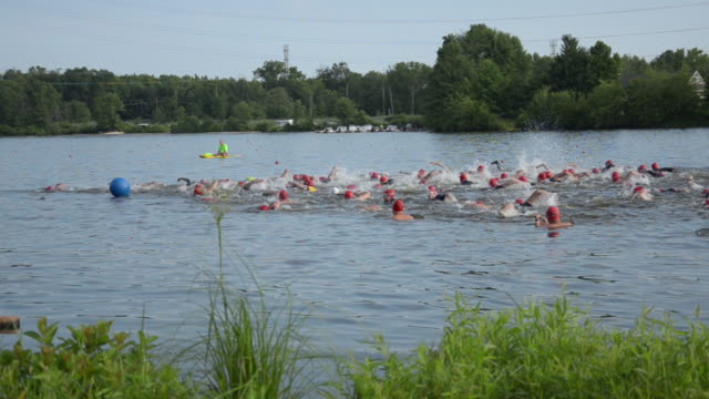triathletes start the swim section at the new jersey state triathlon in mercer county park. shot using steadycam. - vermont stock videos & royalty-free footage