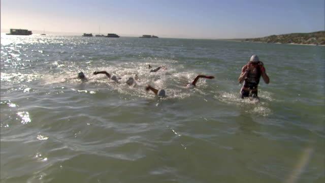 SLO MO WS Triathletes swimming toward shore in Kraalbaai and wading onto beach / Langebaan, South Africa
