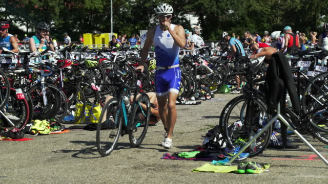 triathletes switching between disciplines in the transition area - triatleta video stock e b–roll