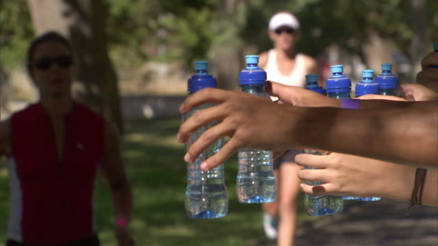 vidéos et rushes de slo mo cu triathletes taking water bottles from supporters while running race in de waal park / cape town, south africa - bouteille d'eau minérale