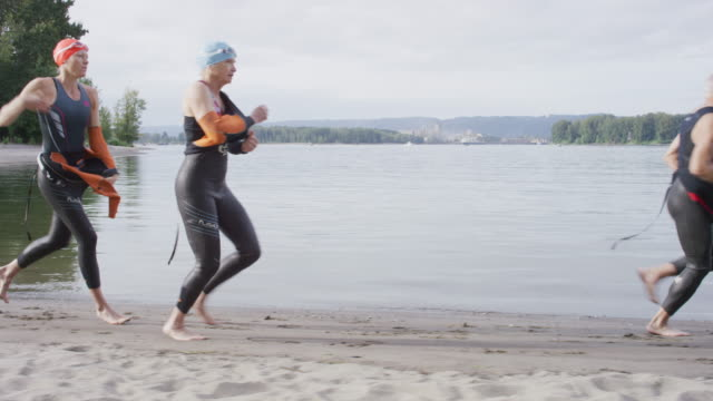 Triathletes taking wetsuits off as they run