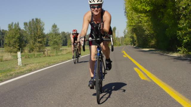 vídeos de stock, filmes e b-roll de os triatletas treinamento para um triatlo andando de bicicletas - triatleta