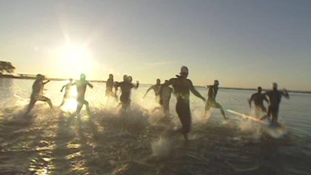 triathlon swim start charge into water sunrise - salmini video stock e b–roll