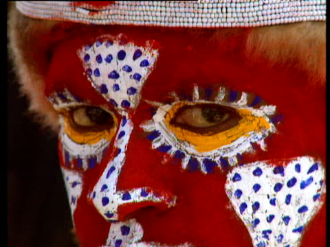 vídeos y material grabado en eventos de stock de tribal boy with face painted red and white looks away from camera - oceania