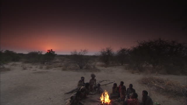 ws cs td tribal families sitting around fire / hadza, tanzania - stamm stock-videos und b-roll-filmmaterial