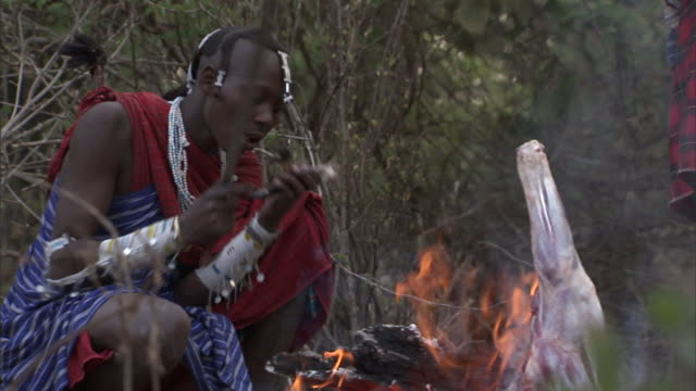 tribal hunters eat by an open fire where a leg of meat cooks. - 動物を使うスポーツ点の映像素材/bロール