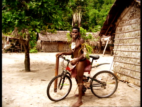 stockvideo's en b-roll-footage met a tribal man wearing a loincloth and facial jewelry walks with a bicycle in a village in fiji. - hoofdtooi