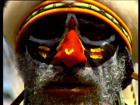 Tribal man's face painted with red paint on nose and white beard