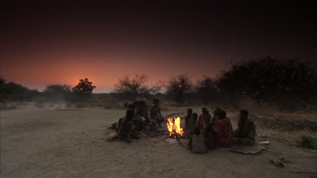 tribal members sit around an open campfire. - stamm stock-videos und b-roll-filmmaterial
