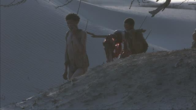 Tribal men and boys carry a fresh kill to their desert village.