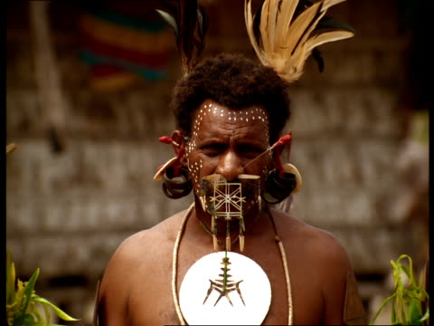 Tribal men in Fiji wear headdresses, jewelry, and makeup designs on their faces.