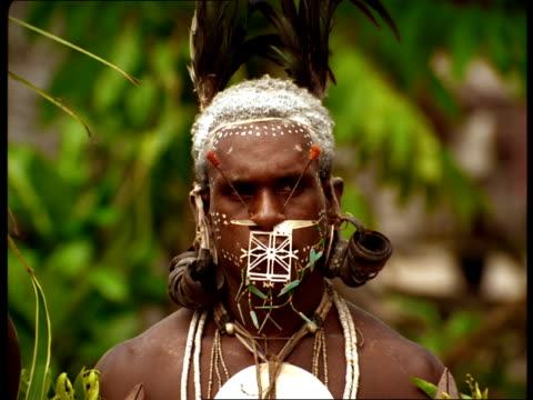 Tribal men in Fiji wear makeup and jewelry and smoke pipes.