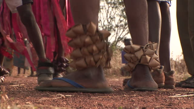tribal men wear sandals, ankle bracelets and flip-flops as they stomp and dance. - minoranza video stock e b–roll