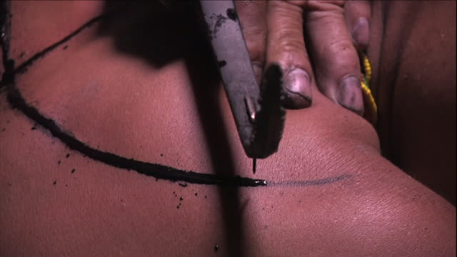 a tribal tattoo artist in indonesia uses a needle and hammer to tattoo a tribesman's back. - indigenous culture stock videos & royalty-free footage