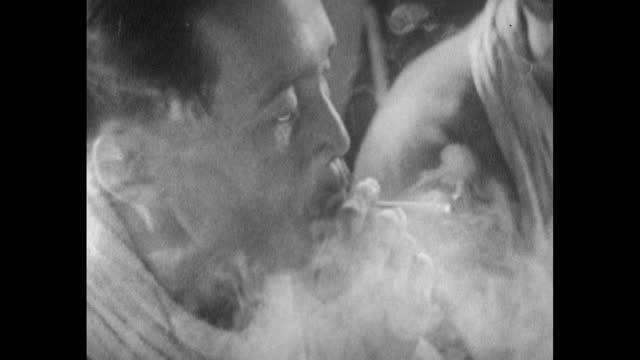 tribesman rolls and smokes a cigarette in sarawak; 1963 - サラワク州点の映像素材/bロール