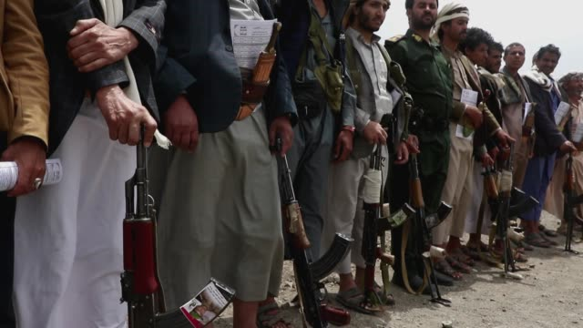 tribesmen loyal to the houthi group hold their guns while they chant slogans during an armed tribal gathering supporting the forces of the houthi... - イエメン点の映像素材/bロール