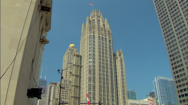 vidéos et rushes de tribune tower w/ american flag on roof partial skyscrapers on left right bg city urban landmark iconic historical historic - tribune tower