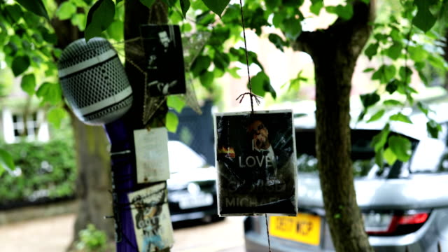tributes to the british musician george michael sit outside his former home in an unofficial memorial garden in highgate on may 25 2018 in london... - shrine stock videos & royalty-free footage