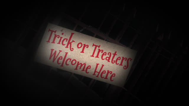 Trick or Treat sign on the gates of a graveyard