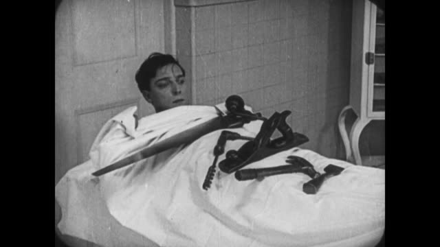 1921 tricky man (buster keaton) hides from police inside hospital jumping from window to escape surgery - 無声映画点の映像素材/bロール