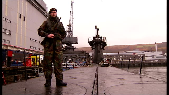 hms vigilant scotland faslane ext armed and uniformed soldier standing guard on outer deck of trident submarine hms vigilant as docked in naval... - trident stock videos & royalty-free footage