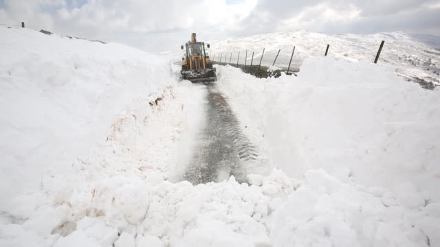 a jcb tries to clear a way through massive snow dr - road closed sign stock videos & royalty-free footage